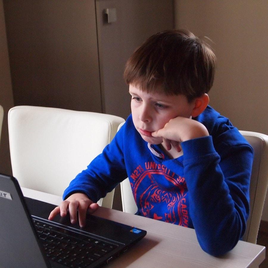baiat folosind un laptop pentru școală