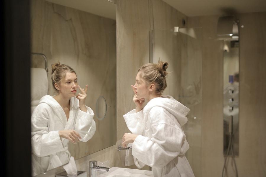 femeie în oglindă aplicând produse antirid