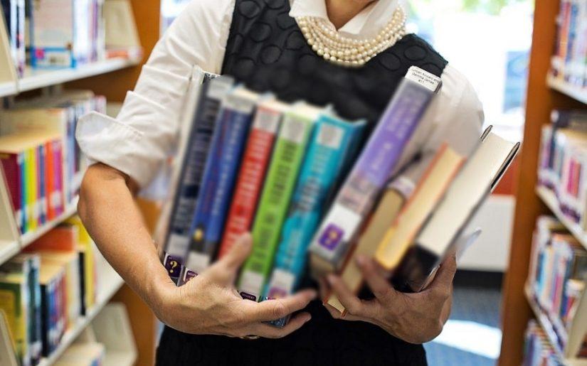 femeie care ține cărți, bibliotecă